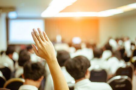businessman raising hand during seminar. Businessman Raising Hand Up at a Conference to answer a question. Imagens