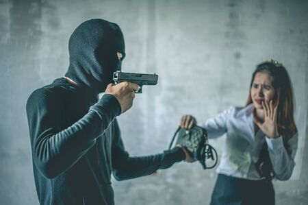 Robber with a gun robbing intimidate a woman surrender.Bandit steals from woman.Crime and robbery concept. Imagens