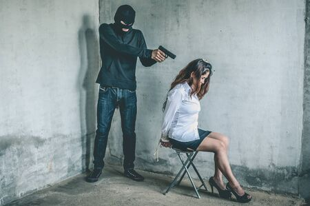 bandit with masked holding gun to Business woman tied.rope hostage concept. Stock Photo