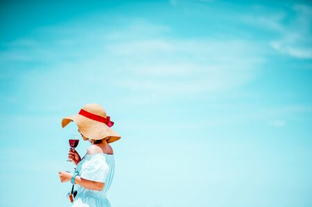 young woman in sun hat on beach over sea and blue sky background.copy space.Minimal Summer holidays.