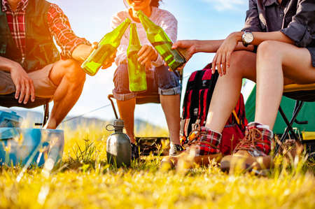Team of asian climbers hiker are sitting and enjoying a drink after a set up outdoor tent in the forest path autumn season. Hiking, hiker, team, forest, camping , activity concept. Standard-Bild