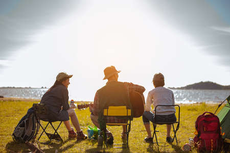 Team of asian climbers hiker are sitting and enjoying a drink after a set up outdoor tent playing music together in the forest path autumn season. Hiking, hiker, team, forest, camping, activity concept.