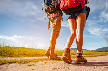 Young couple asian in a wide field is walking on foot to explore the forest as a holiday activity in the forest path autumn season. Hiking, hiker, team, forest, camping, activity concept.