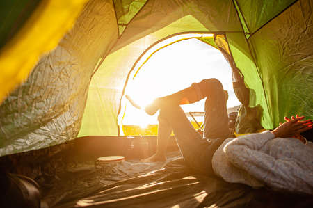 The woman asian who just woke up inside the tent was watching the sunrise in the morning as a holiday activity in the forest path autumn season. Hiking, hiker, alone, forest, camping, activity concept.
