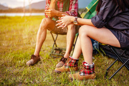 Male and female asian travelers are sitting and enjoying a drink after a set up outdoor tent in the forest path autumn season. Hiking, hiker, team, forest, camping , activity concept.
