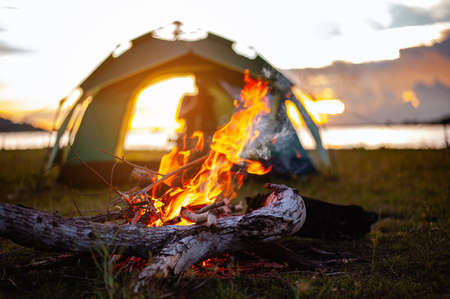Camping bonfire surrounded by team of asian climbers hiker, they are playing music together in the forest path autumn season. Hiking, hiker, team, forest, camping , activity concept. Standard-Bild