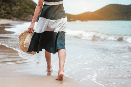 Happy asian women with holding hat walking barefoot to receive the wind and enjoy life on the beach vacation. beach, summer, liftstyle, positive mood, travel, relax concept.