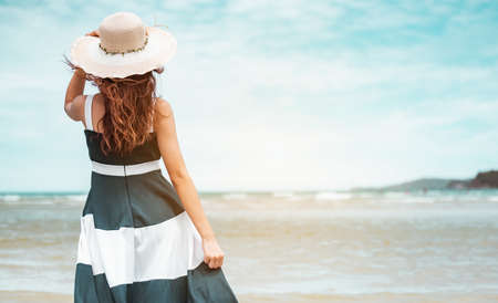 Happy asian women with holding hat stand to receive the wind and enjoy life on the beach vacation. beach, summer, liftstyle, positive mood, travel, relax concept. Standard-Bild