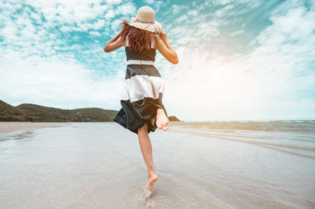 Happy asian women with holding hat running and jump joyfully enjoy life on the beach vacation. beach, summer, liftstyle, positive mood, travel, relax concept. Standard-Bild