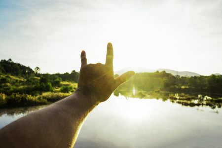 Use hand to touch the sun light in the morning, Love sign, Yellow light with cold air, Flare light from sunrise, holding sun rays, Symbols of hope, pray for god