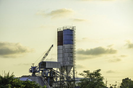 Concrete mixing tank on sunset sky clouds, Grinding and Mixing concrete tank, Industrial concept, Orange sunset light with landscape nature tree