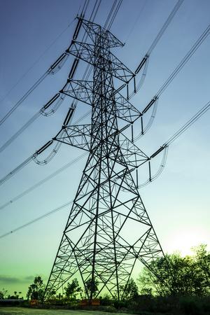Poste de electricidad con silueta del cielo del atardecer, Torre de electricidad con sombra de árbol en el amanecer, Línea de transmisión de energía eléctrica en la puesta del sol con espacio de copia, Torre de electricidad en el cielo naranja Foto de archivo