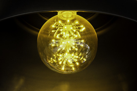 Close up incandescent lamp shining, Yellow light of lamp hang on ceiling Banco de Imagens