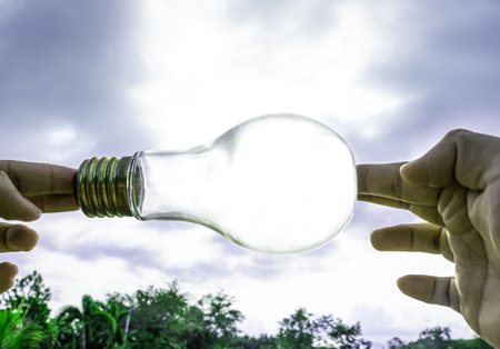 Hand holding light bulb with sunset sky, Use hand hold incandescent lamp for electricity for life concept, Energy saving concept, Incandescent lamp with green nature against the blue sky