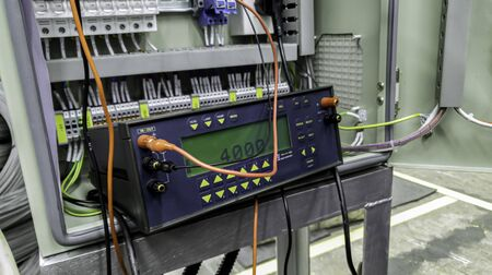 Voltage source calibrator device with control panel in factory site, Current and Voltage source instrument checking, Voltage measuring instrument hang on main braker substation
