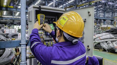 Blur background of electrical engineer are working on factory site, Technician check fault in power control unit on factory site, Electrician are checking fault in control box