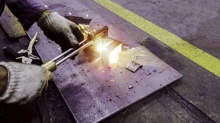 Cutting metal plate by gas flame, Worker are welding metal work in factory