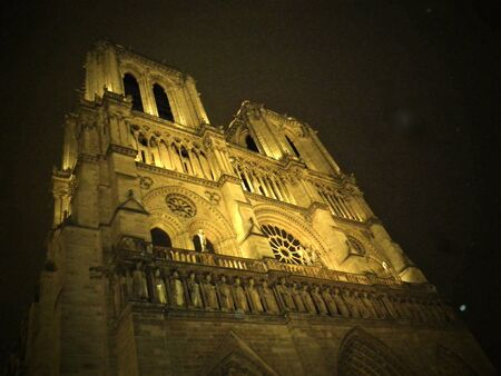 A picturesque view of The Cathedral of Notre Dame at night in Paris, France