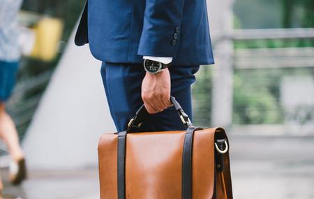 Nahaufnahme eines Geschäftsmannes tragen die Uhr und halten den ledernen Aktenkoffer, der geht, mit dem Sonnenschein zu arbeiten Standard-Bild - 74554553
