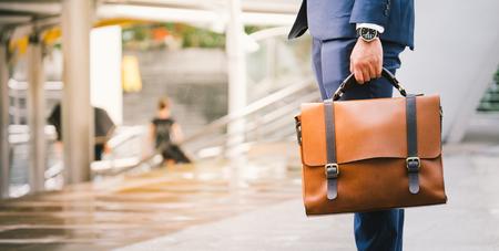Primer plano de un hombre de negocios llevar el reloj y la celebración de maletín de cuero va a trabajar con el sol Foto de archivo - 74554557