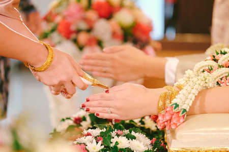 Hands pouring blessing water into brides bands, Thai wedding