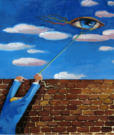a man behind a wall makes flying a kite in the shape of an eye