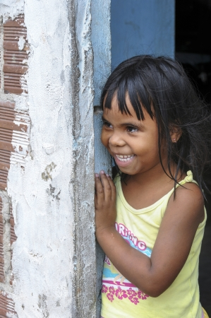 observant: Smiling little girl in a suburb of a Brazilian city  JOAO PESSOA, PB - OCT 20  Unidentified little girl of the suburbs smile curious on Oct 20, 2008 in Joao Pessoa, Brasil