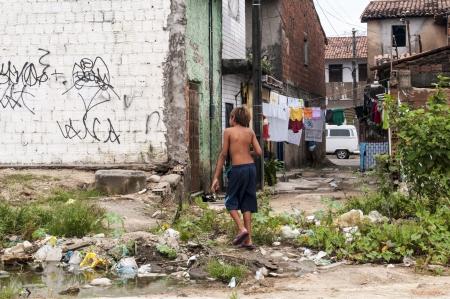 penury: Boy in a poor and dirty neighborhood of suburbs, Fortaleza, BrazilFORTALEZA, CE - MAY 14: Unidentified boy in a poor and dirty favela on May 14, 2011 in Fortaleza, Brasil. Editorial