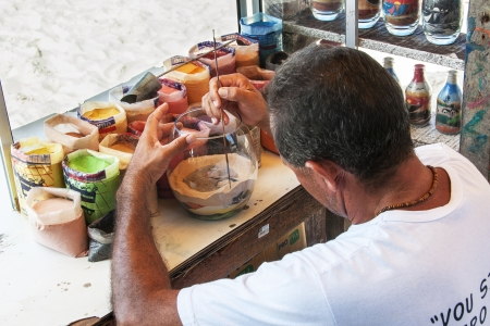 Sand Art. Craftsman using colored sand make landscapes scene in bottle or glasses on June 19 2011, in Fortaleza, Brazil