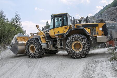 Buldozer in a granite quarry on the Alps photo