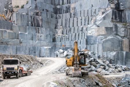 Buldozer et camion dans une carrière de granit sur les Alpes