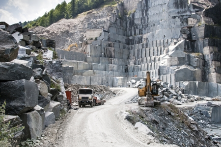 Buldozer and truck in a granite quarry on the Alps photo