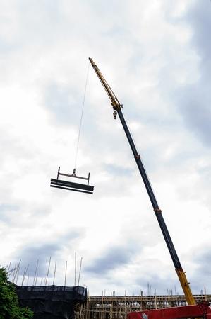 hijsen: Kraan hijst betonplaat op bouwplaats