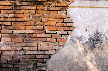 split up: Cracked cement wall see to brick in side a background Stock Photo