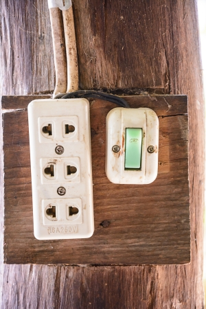 switch plug: Electrical switch and plug box installed on wooden pole
