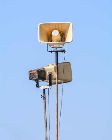 Old loudspeakers on steel pole on blue sky photo
