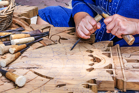 mastery: Hands of the craftsman carving a bas-relief
