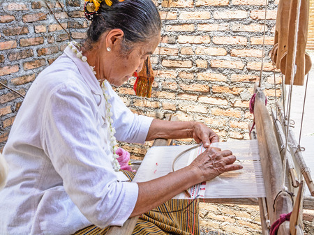 CHIANGMAI, THAILAND - APRIL 14  Unidentified old woman was weaving cotton on April 14, 2014 in Chiang Mai, Thailand
