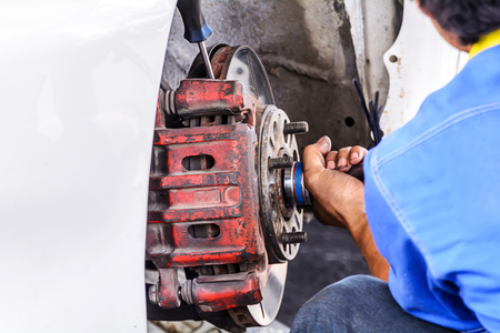 disassembly: Mechanic technician worker replacing brakes vehicle of automobile at repair service station