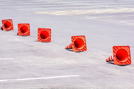 Orange traffic warning cones in row  on the parking area photo