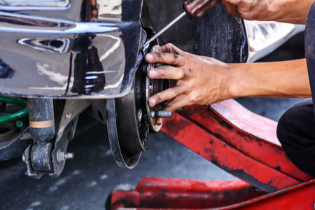 Mechanic technician worker replacing brakes vehicle of automobile at repair service station