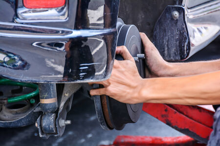 scheduled replacement: Mechanic technician worker replacing brakes vehicle of automobile at repair service station