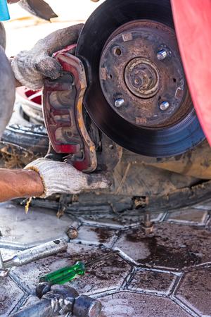 frenos: T�cnico Mec�nico trabaj� reemplazar los frenos del veh�culo del autom�vil en la estaci�n de servicio de reparaci�n. Foto de archivo
