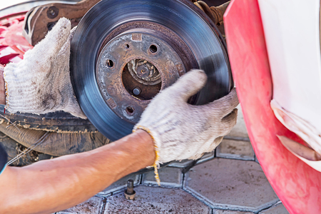 service station: Mechanic technician worked replacing brakes vehicle of automobile at repair service station.