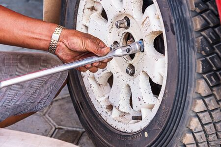 disassembly: Mechanic technician worker replacing wheel vehicle of automobile at repair service station.