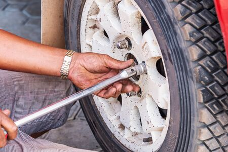 scheduled replacement: Mechanic technician worker replacing wheel vehicle of automobile at repair service station.