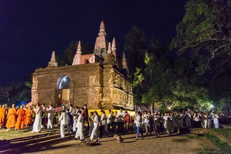 CHIANG MAI THAILAND  JUN 01: Clergy and Buddhists candle lit around mock bodh gaya pagoda in Vesak Day at Jed Yod temple on June 01 2015 in Chiang Mai Thailand.