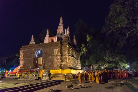 clergy: CHIANG MAI THAILAND  JUN 01: Clergy and Buddhists candle lit around mock bodh gaya pagoda in Vesak Day at Jed Yod temple on June 01 2015 in Chiang Mai Thailand.