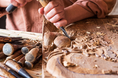 Hands of the craftsman wooden carving a bas-relief.