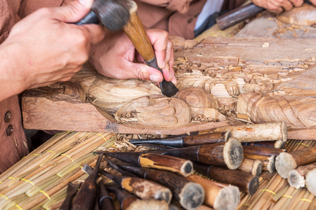 mastery: Hands of the craftsman wooden carving a bas-relief.